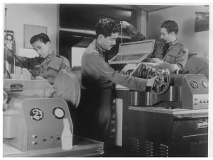 """Subtte. Ramón Caracas Enriquez (al centro), en el laboratorio de Inteligencia Aérea revisando películas de las """"Gun Cams"""" (Cámaras de arma), que se colocaban en substitución de una de las ametralladoras Cal. 0.50 de los aviones P-47D para que una vez que abrieran fuego, simultáneamente filmaran, a fin de observar y reconocer los daños ocasionados a un blanco enemigo. Material propiedad de la AMV II GM A.C."""